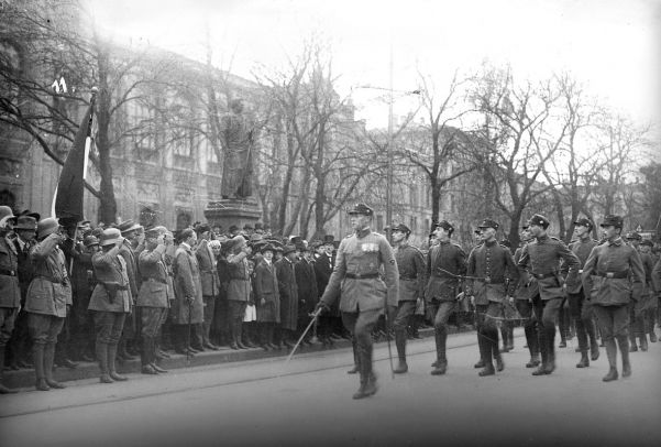 The SA marches to the War Memorial in Munich in 1923. A hatless Hitler reviews the parade from the pavement.