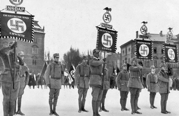 SA men carry Deutschland Erwache (Germany Awake) standards at the 1st Nazi Party Day, January 1928.