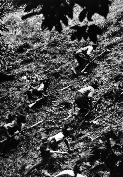 Japanese troops cautiously scale a hill during their advance to Singapore