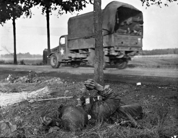 A US truck races past the corpse of a German soldier during the Allied drive to liberate Holland