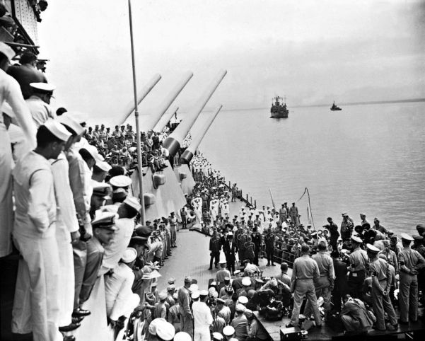 Sailors and officials on the deck of the USS Missouri witness the Japanese sign surrender documents in Tokyo Bay