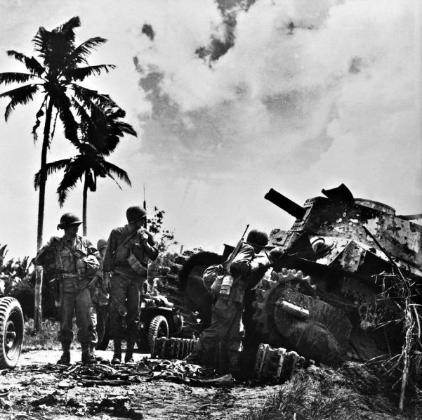 Following their unopposed landing, troops of the US Sixth Army examine a knocked-out Japanese tank of Luzon