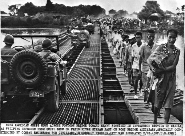 As fighting rages in and around Manila, the capital of the Philippines, refugees pour out of the city. This bridge was built by US engineers