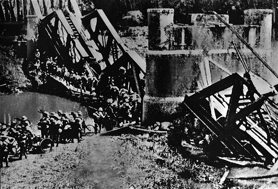 Japanese troops pass a destroyed railroad bridge as they enter Burma from neighboring Thailand