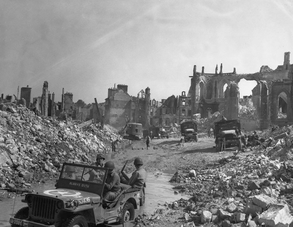 Allied troops in the ruins of Valognes during the drive against Cherbourg, which fell on June 29, 1944